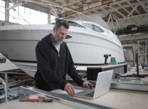 Worker Using Laptop While Working With Metal Parts Near Boat In Workshop